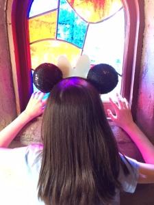 Sherry's granddaughter looks into the stain glass window of Sleeping Beauty's castle